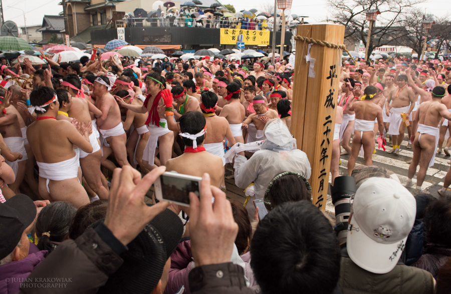 Festival participants wearing nothing but traditional Japanese underwear are reaching the main gate of Konomiya Shrine.