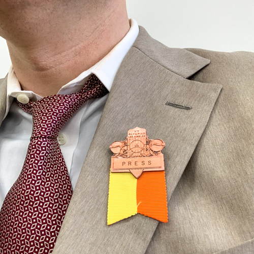 A reporters badge pinned to a jacket.