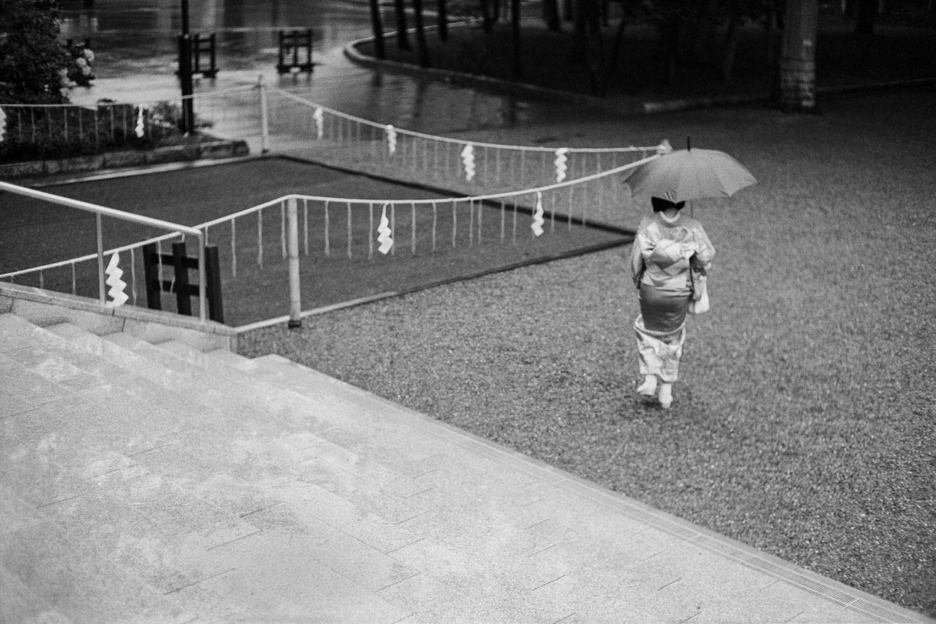 Japanese woman in a kimono holding an umbrella, walking away from a shrine.
