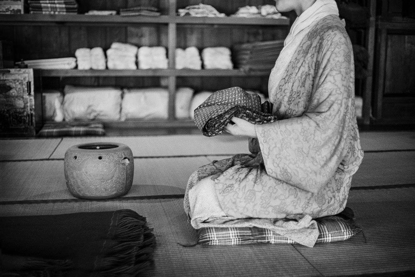 Japanese woman in kimono kneeling on tatami mat.