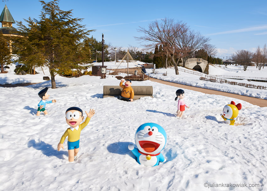Manga character Doraemon and his friends covered in snow in a park.