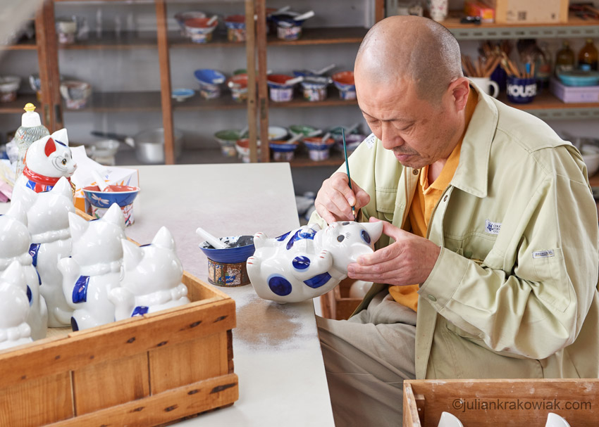 Artisan painting a pottery cat